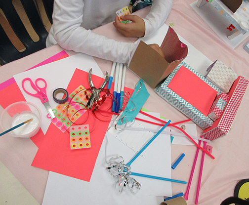 Student holding stickers and working with an assortment of materials on the table.