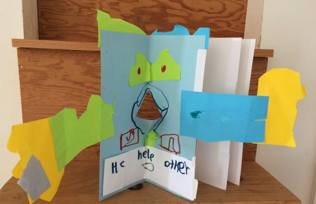 "A child's book with a figure that has a pop up nose and long arms made from paper. The text says, ""He help other."""